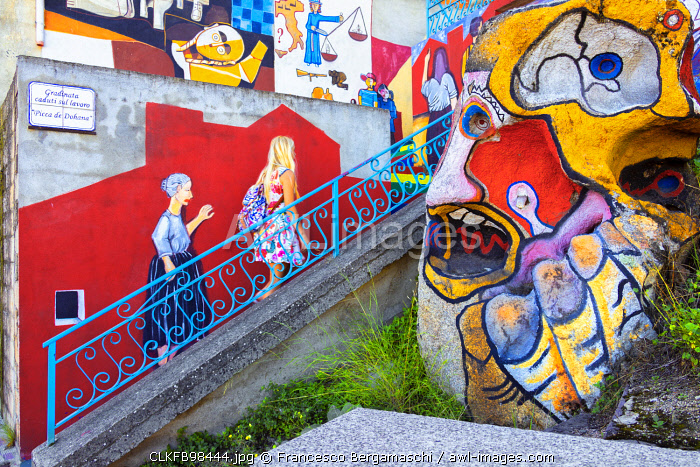 A girl walks on a painted staircase in the village of Orgosolo, Nuoro province, Sardinia, Italy, Europe. (MR)