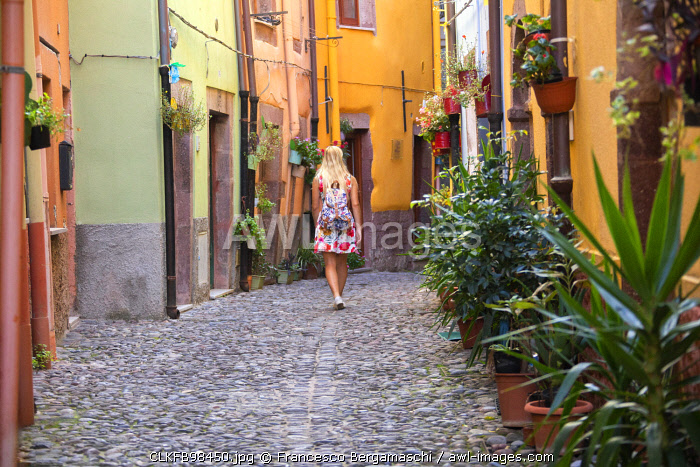 A girl walks in a street of Bosa, Oristano province, Sardinia, Italy, Europe. (MR)