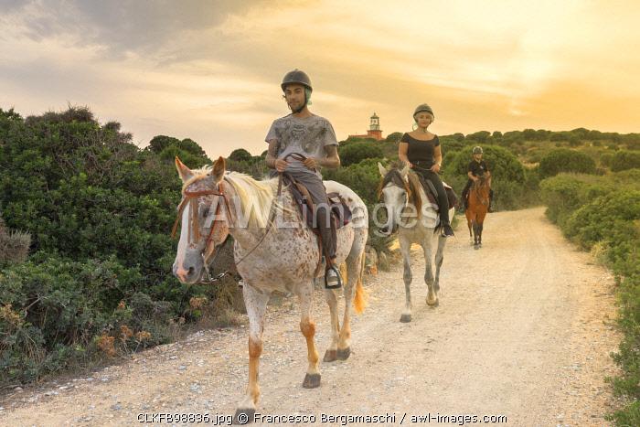 Tourists practice horse riding near the lighthouse of Capo Spartivento, Domus de Maria, Cagliari province, Sardinia, Italy, Europe.