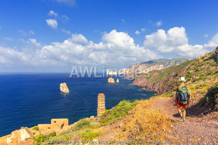 A tourist walks on a path for Laveria Lamarmora, Nebida, Iglesias, Sud Sardegna province, Sardinia, Italy, Europe. (MR)
