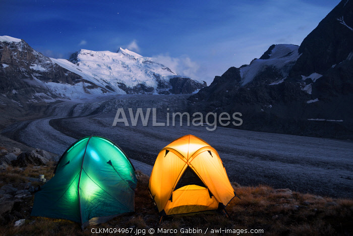 Illuminated tents by nigh camping close to the Grand Combin glacier, Grand Combin on background,Switzerland