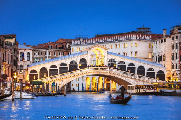 Rialto bridge and gondola on the Grand Canal at dusk, Venice, Italy
