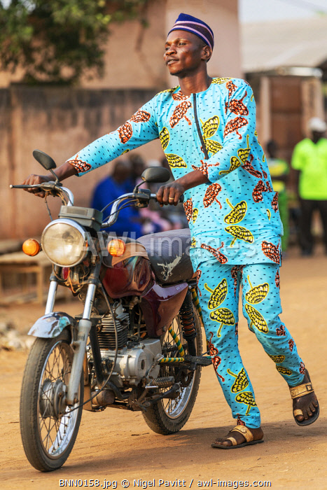 Benin, Ouidah, Atlantique Department.  A motor cyclist in bright traditional dress.