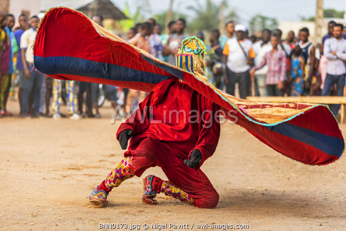 Benin, Ouidah, Atlantique Department.  An Egungun masked dancer spins his decorated round cape at a lively voodoo celebration.  The dancers represent Yoruba ancestral spirits which give guidance to the living.