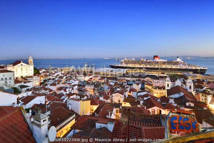 awl-images.com - Portugal / The iconic cruise ship Queen Mary II on the Tagus river facing the traditional moorish Alfama district. Lisbon, Portugal