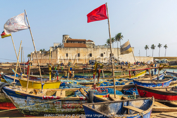 Africa, Ghana, Elmina harbour. Traditional wooden fishing boats in the harbour in front of the famous castle.
