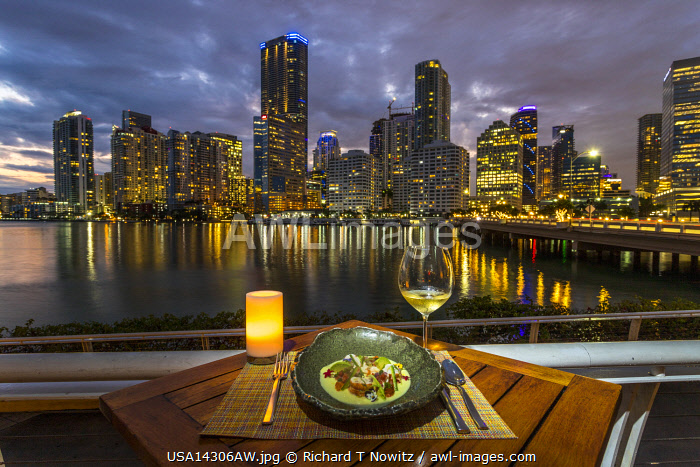 USA, Florida, Miami downtown business district seen from Mandarin Oriental Hotel restaurant veranda with seafood entree.