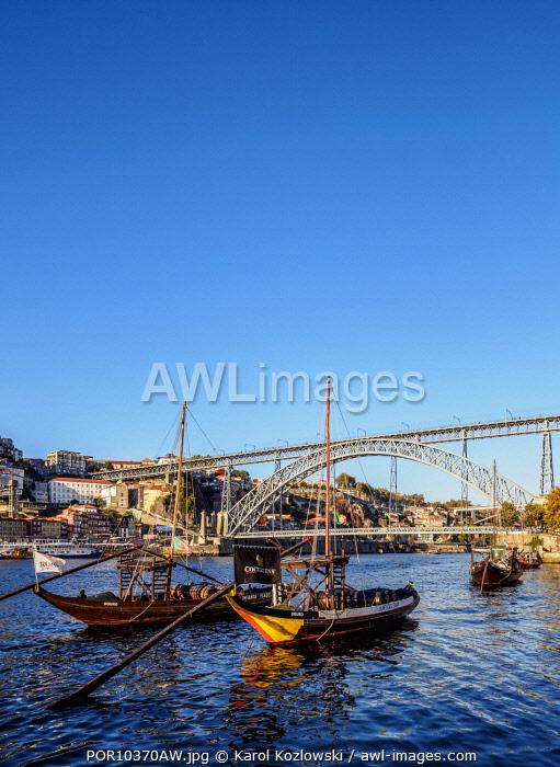 Traditional boats on Vila Nova de Gaia bank of Douro River, Dom Luis I Bridge in the background, Porto, Portugal