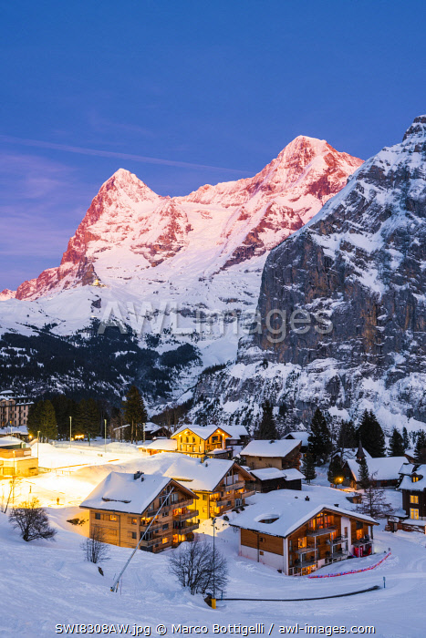 awl-images.com - Switzerland / Mürren, Berner Oberland, canton of Bern, Switzerland. The village with Eiger and Mönch in the backdrop at dusk