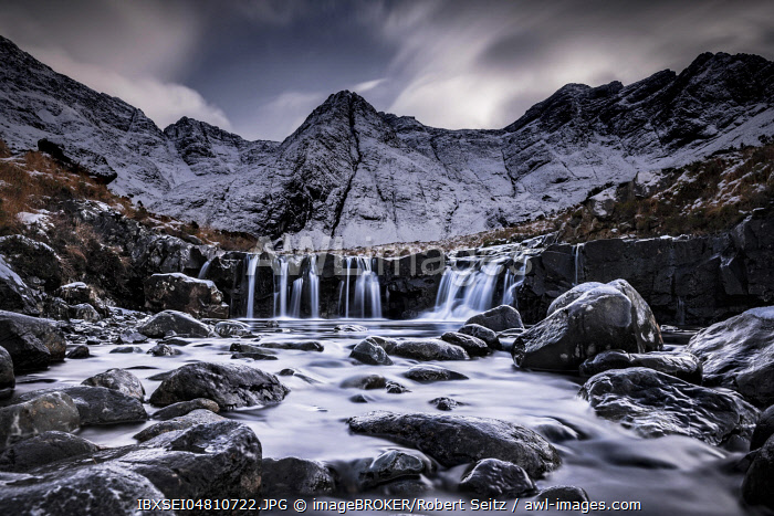 Small river with waterfall in snowy landscape with winter Cullins mountains in the background, Carbost, Portree, Isle of Skye, Scotland, United Kingdom, Europe