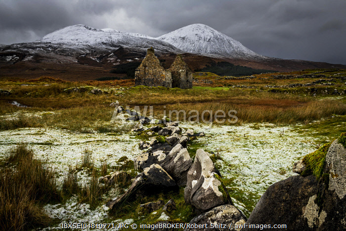Rock row with white caps and house ruin in Highland scenery with snowy Cullin mountains in the background, Broadford, Isle of Skye, Scotland, United Kingdom, Europe