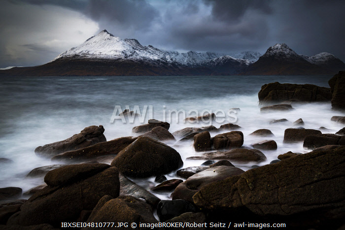 Big rocks in the water of the North Sea with snow-covered Cullin mountains in the background, Elgol, Isle of Skye, Scotland, United Kingdom, Europe