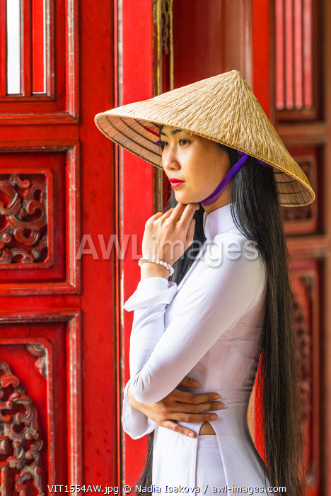 Young woman wearing traditional national costume, ao dai, in the Imperial City, Hue, Vietnam