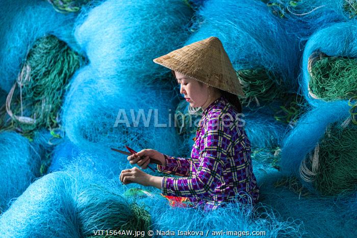 A Vietnamese woman mending blue fishing net, Mekong Delta, Vietnam
