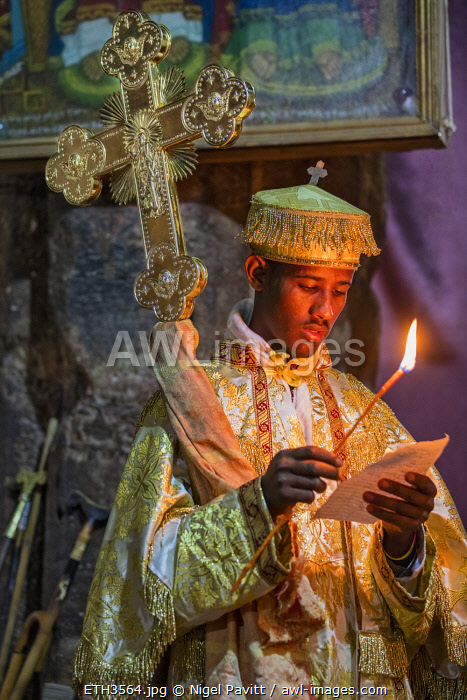 Ethiopia, Abraha Atsbeha, Tigray Region.  A deacon with a large crossreads by the light of a taper in the rock-hewn church of Abraha wa-Atsbeha during a midnight mass to celebrate Enkutatash, the Ethiopian New Year.