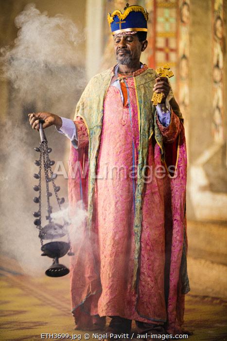 Ethiopia, Lake Tana, Dek Island, Amhara Region. A priest in the eighteenth century church at Narga Selassie swings a censer among clouds of incense.