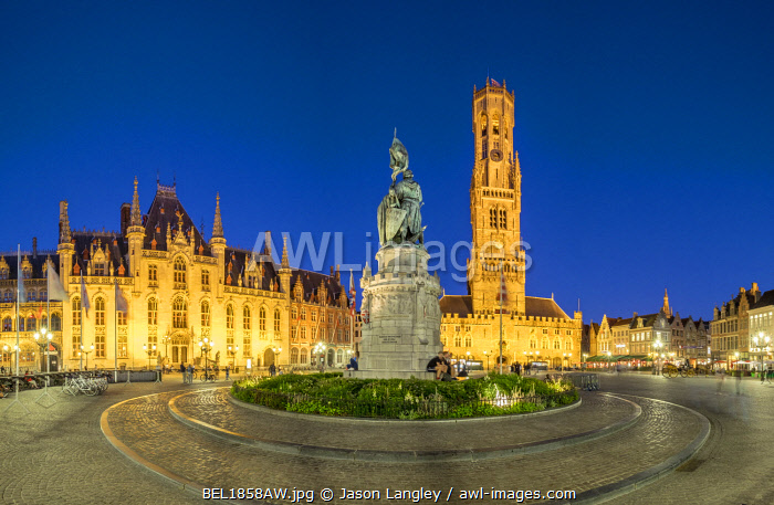 Belgium, West Flanders (Vlaanderen), Bruges (Brugge). Belfort van Brugge belfry tower and Statue of Jan Breydel and Pieter de Coninck on Markt square at dusk.