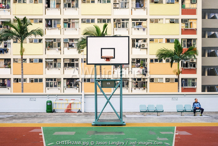 Man sitting on basketball court at Choi Hung Estate, one of the oldest public housing estates in Hong Kong, Wong Tai Sin District, Kowloon, Hong Kong, China