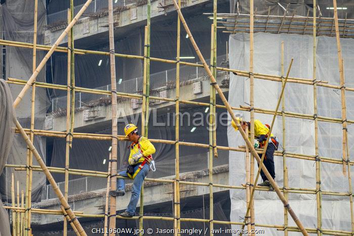 Workers constructing a bamboo scaffolding at building site of skyscraper, Tsim Sha Tsui, Kowloon, Hong Kong, China