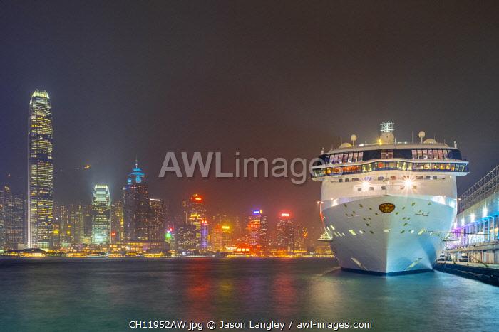 Star Cruises cruiseliner at Ocean Terminal cruise terminal and buildings on Hong Kong Island at night, Tsim Sha Tsui, Kowloon, Hong Kong, China