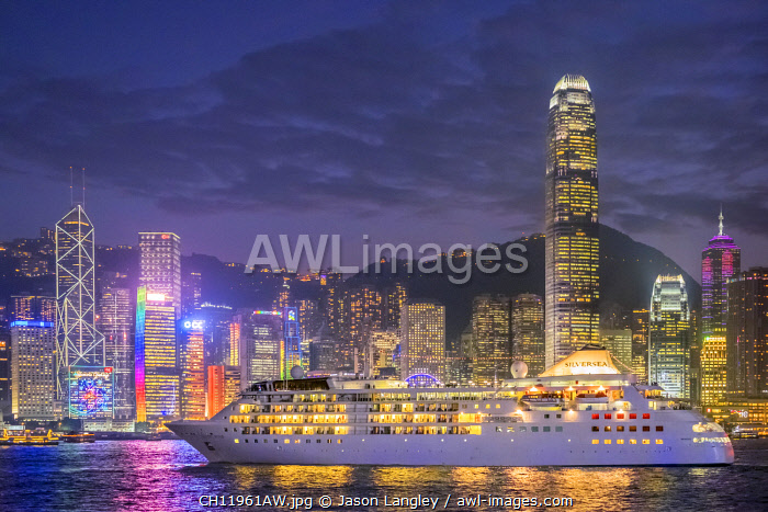 Cruisliner Silversea passing by Hong Kong Island skyline on Victoria Harbor at night, Hong Kong, China