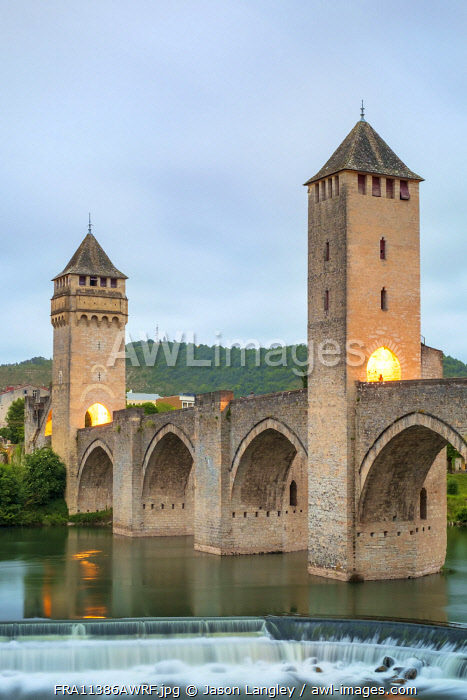 Medieval Pont Valentré bridge over the Lot River at dawn on cloudy morning, Cahors, Lot Department, Midi-Pyrénées, France