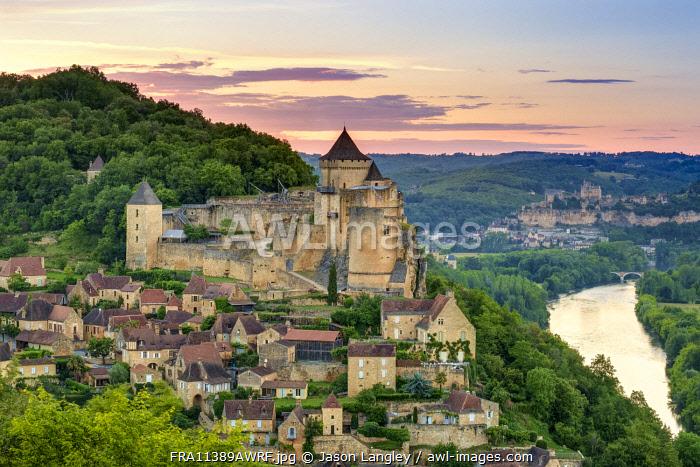 Chateau de Castelnaud castle and village over Dordogne River valley at sunset, Castelnaud-la-Chapelle, Dordogne Department, Aquitaine, France