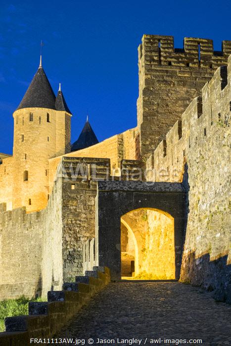 Porte d'Aude city gates entrance to medieval citadel of La Cité at night, Carcassonne, Aude Department, Languedoc-Roussillon, France.