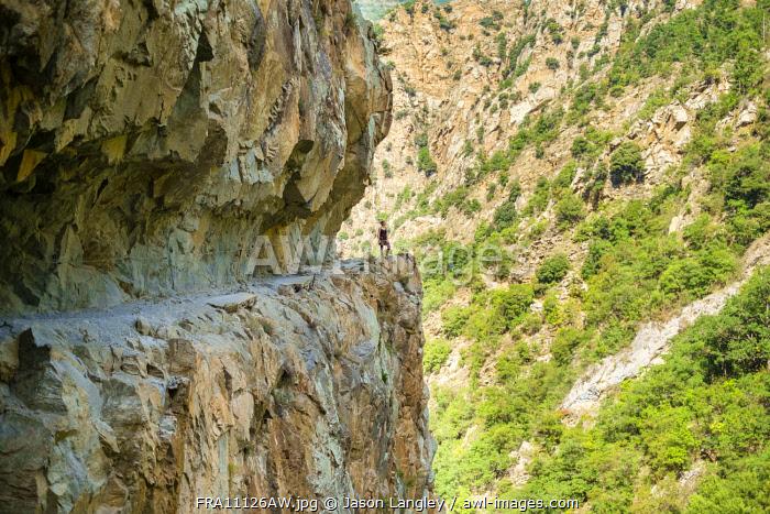 A hiker stands next to edge of cliff in the Gorges de la Carança, Pyrénées-Orientales, Languedoc-Roussillon, France.