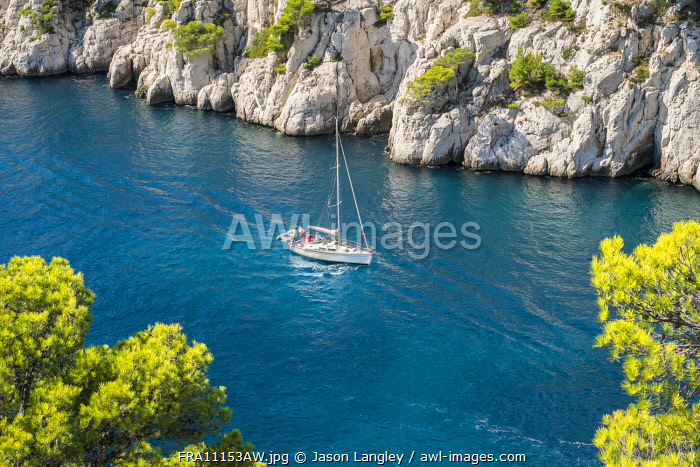 Sailboat passing through emerald blue water of Calanque de Port-Pin, Cassis, Bouches-du-Rhône, Provence-Alpes-Côte d'Azur, France.