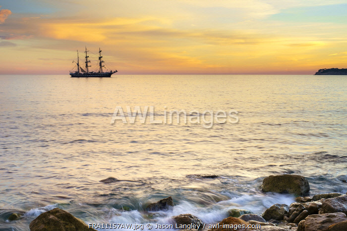 Silhouette of sailing ship at sunset off the coast of Cassis, Bouches-du-Rhône, Provence-Alpes-Côte d'Azur, France.