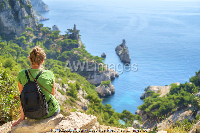 Young woman hiker sitting above Calanque de Sugiton, Parc National des Calanques, Bouches-du-Rhône, Provence-Alpes-Côte d'Azur, France. (MR)