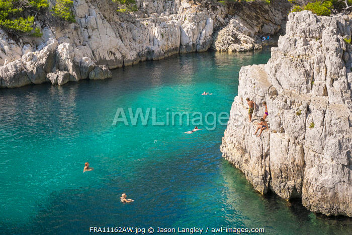 Children jumping from a rock in the Calanque de Sugiton, Parc National des Calanques, Bouches-du-Rhône, Provence-Alpes-Côte d'Azur, France
