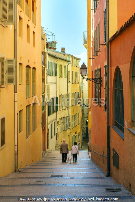 Two people walking down stairs between colorful buildings, Vieille Ville (old town), Nice, Alpes-Maritimes, Provence-Alpes-Côte d'Azur, France.