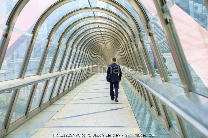 Man walking through Japan Bridge covered skywak in La Défense business district, Paris, Île-de-France, France.