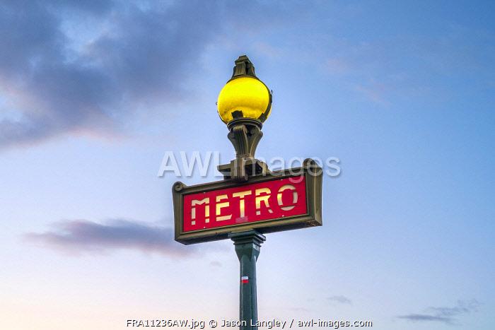 Illuminated Metro sign at sunrise, Paris, Île-de-France, France