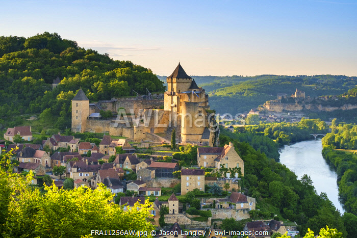 Chateau de Castelnaud castle and village over Dordogne River valley in late afternoon, Castelnaud-la-Chapelle, Dordogne Department, Aquitaine, France
