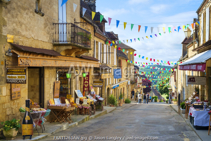 People and shops along street in Domme, Dordogne Department, Aquitaine, France