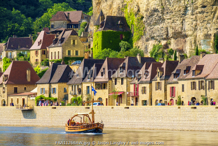 Tourist boat passing in front of old stone houses on Dordogne River in late afternoon, La Roque-Gageac, Dordogne Department, Aquitaine, France