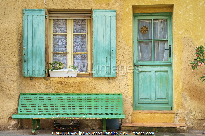 Cat sleeping under a bench in front of a house in Roussillon, Vaucluse, Provence-Alpes-Côte d'Azur, France