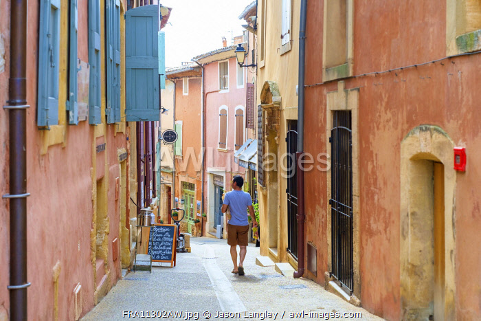 French man walking through streets of Roussillon carrying a baguette, Vaucluse, Provence-Alpes-Côte d'Azur, France