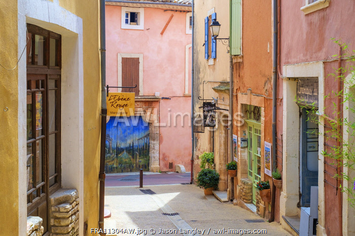 Colorful ochre colored buildings on a street in Roussillon, Vaucluse, Provence-Alpes-Côte d'Azur, France