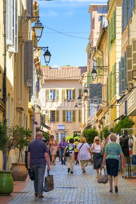 Shoppers walking past colorful buildings on main shopping street Rue Felix Pijeaud, Sanary-sur-Mer, Var department, Provence-Alpes-Côte d'Azur, France