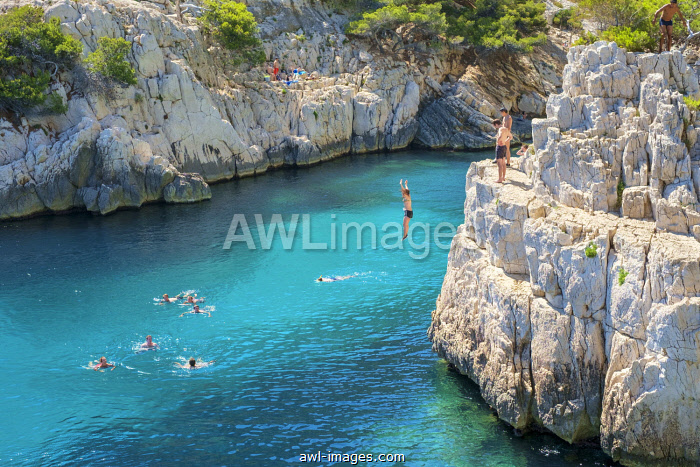 People jumping into beautiful blue water from a rocky outcrop at Calanque de Sugiton, Parc National des Calanques, Provence-Alpes-Côte d'Azur, Bouches-du-Rhône, France