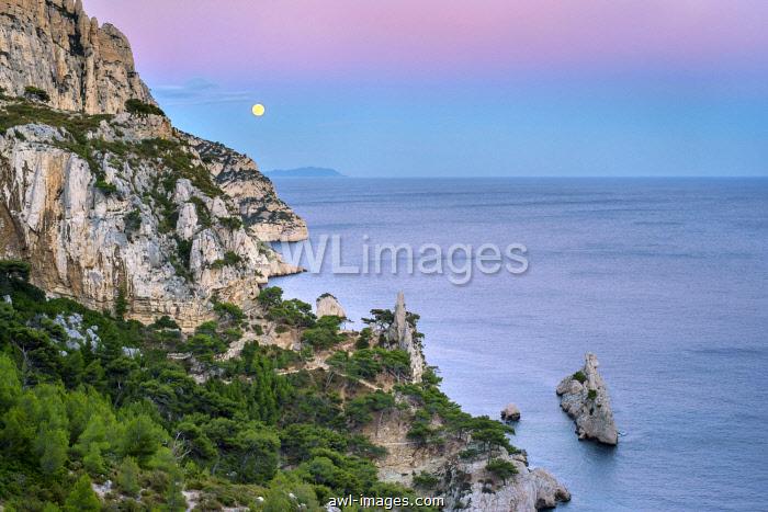 Full moon rising over ocean and Mediterranean landscape at Calanque de Sugiton after sunset, Parc National des Calanques, Provence-Alpes-Côte d'Azur, Bouches-du-Rhône, France