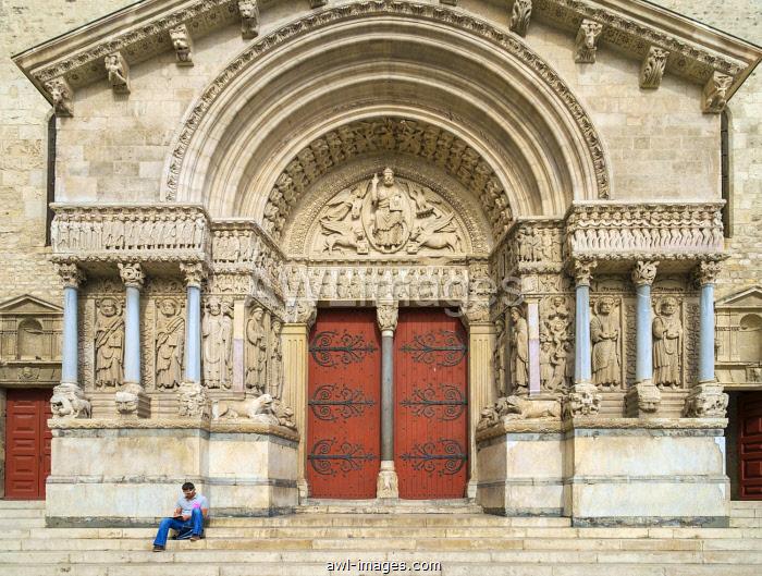 Man sitting in front of portal entrance ot Cathédrale Saint-Trophime d'Arles (Church of St. Trophime), Arles, Provence-Alpes-Côte d'Azur, Bouches-du-Rhône, France