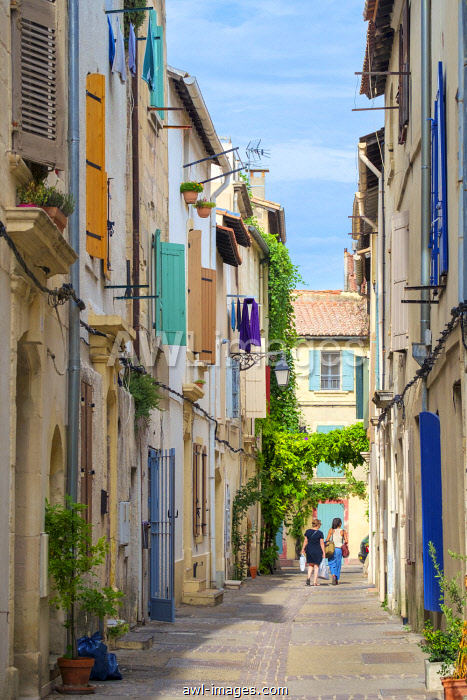 Two woman walking down colorful alleyway in Arles old town, Provence-Alpes-Côte d'Azur, Bouches-du-Rhône, France