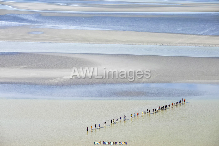 France, Normandy (Normandie), Manche department, Le Mont-Saint-Michel. People walk through the mudflats surounding the mount at low-tide.