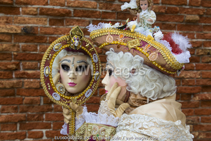 Venice, Italy. Carnival with models dressed in costumes and masks looking at mirror
