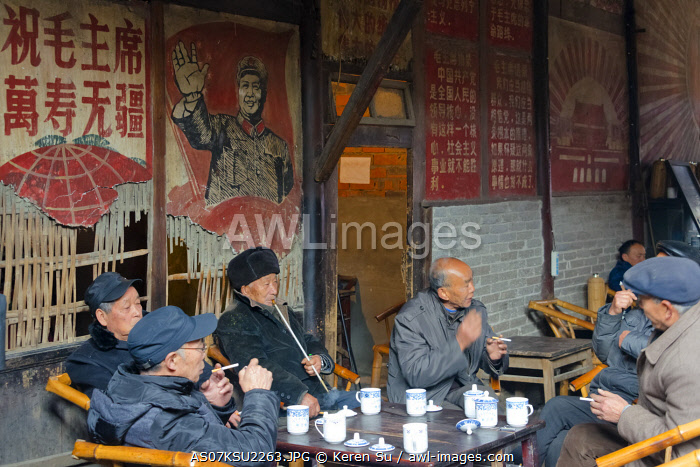 awl-images.com - China / Old man smoking a pipe in a teahouse decorated with Cultural Revolution-era portrait of Chairman Mao, Pengzhen, Chengdu, Sichuan Province, China